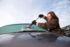 Kvinna som skrotar frost av hennes vindruta i vintern Royaltyfri Bild
