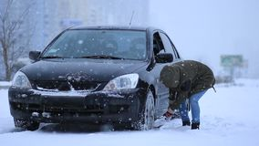 Kvinna som skyfflar och tar bort snö från hennes bil lager videofilmer