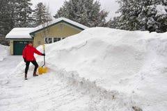 Kvinna som skyfflar snö från körbanan Arkivbilder
