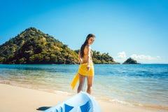 Kvinna som släpar hennes fartyg till vattnet på stranden Royaltyfri Fotografi