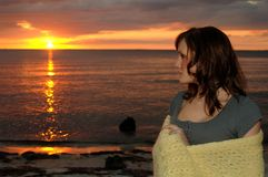 Kvinna som slås in i filt på solnedgången royaltyfri bild
