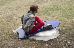 Kvinna som sledding på litet belopp av snö Royaltyfria Bilder