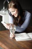 Kvinna som smsar på hennes telefon Arkivfoto