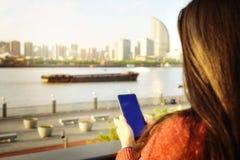 Kvinna som smsar p? smartphonen bredvid floden i sommars?song arkivbild