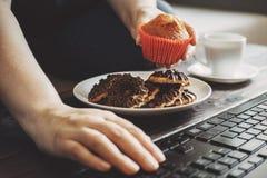 Kvinna som snacking med sötsaker på arbetsplatsen Royaltyfri Foto