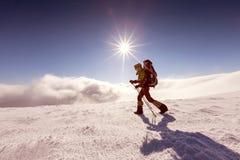 Kvinna som snowshoeing i vinterberg Arkivfoto
