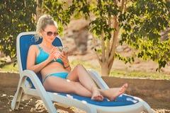 Kvinna som solbadar i bikini på den tropiska semesterorten Härlig kvinna som ligger på soldagdrivare Arkivfoto