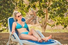 Kvinna som solbadar i bikini på den tropiska semesterorten Härlig kvinna som ligger på soldagdrivare Royaltyfri Foto