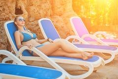 Kvinna som solbadar i bikini på den tropiska semesterorten Härlig kvinna som ligger på soldagdrivare Solsignalljus Royaltyfri Bild