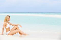 Kvinna som solbadar på härlig strandferie Arkivfoton
