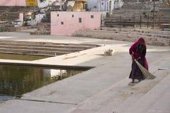 Kvinna som sopar på ghaten royaltyfri fotografi