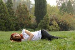 Kvinna som sovar i gräset arkivfoton
