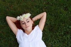 Kvinna som sovar i gräset arkivfoto