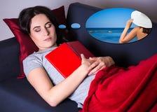 Kvinna som sover med boken på den hemmastadda soffan och drömmer om trav royaltyfri foto