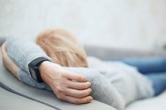 Kvinna som sover med den smarta klockan arkivfoton