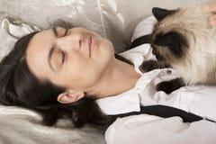 Kvinna som sover med katten Arkivbild