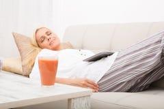 Kvinna som sover med minnestavlan på soffan Arkivbilder