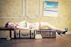 Kvinna som sover på bagaget Arkivfoto