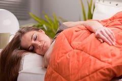 Kvinna som sover slappt på hennes soffa royaltyfri foto