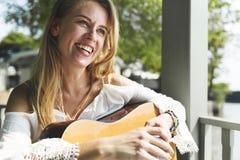 Kvinna som spelar begrepp för gitarrfritidhobby Arkivfoton