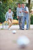 Kvinna som spelar boule med gruppen av pensionärer Royaltyfria Bilder