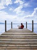 Kvinna som spelar den akustiska gitarren vid sjön Arkivfoton