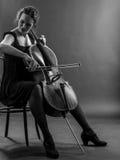 Kvinna som spelar den svartvita violoncellen Arkivbild