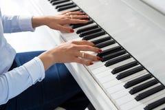 Kvinna som spelar det vita pianot arkivfoton