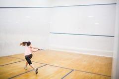 Kvinna som spelar en lek av squash Arkivfoton