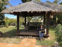 Kvinna som spelar en ukulele i trädgården royaltyfri fotografi