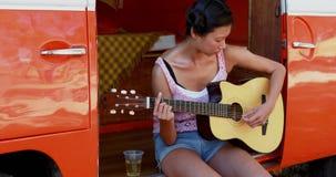 Kvinna som spelar gitarren i campareskåpbilen 4k lager videofilmer