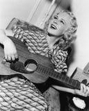 Kvinna som spelar gitarren och att sjunga Fotografering för Bildbyråer