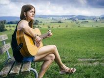 Kvinna som spelar gitarren på en parkerabänk royaltyfri foto