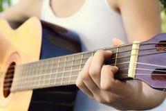 Kvinna som spelar gitarren på parkera royaltyfri fotografi
