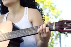 Kvinna som spelar gitarren på parkera fotografering för bildbyråer