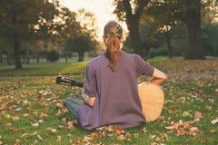 Kvinna som spelar gitarren på solnedgången i parkera Royaltyfria Foton