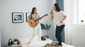 Kvinna som spelar gitarrgrabben som sjunger i fjärrkontroll och hemma dansar på säng stock video