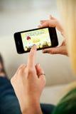 Kvinna som spelar ilskna fåglar på Apple iPhone 4 Arkivbilder
