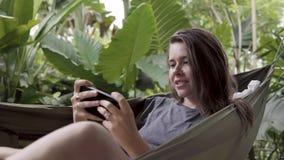 Kvinna som spelar leken på mobiltelefonen, medan sitta på hängmattan arkivfilmer