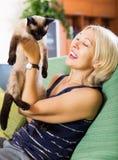 Kvinna som spelar med den Siamese kattungen Royaltyfri Foto