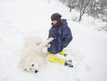 Kvinna som spelar med en vit hund i snön arkivfoto