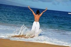 Kvinna som spelar med havvågor Arkivfoto