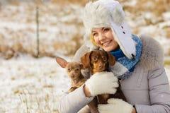 Kvinna som spelar med hundkappl?pning under vinter royaltyfri foto