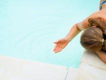 Kvinna som spelar med vatten i simbassäng Arkivfoto