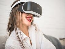 Kvinna som spelar med virtuell verklighetexponeringsglas i hem Arkivbild