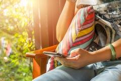 Kvinna som spelar mobiltelefonen i kafé Arkivbild