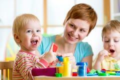 Kvinna som spelar och undervisar med ungar arkivfoto