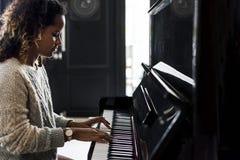 Kvinna som spelar på ett piano royaltyfri foto