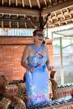 Kvinna som spelar på traditionella det gamelan Balinesemusikinstrumentet man för bali town för solnedgång för form för härlig ind arkivfoto
