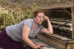 Kvinna som spelar träpianot i öknen, tankfullt uttryck Arkivfoton